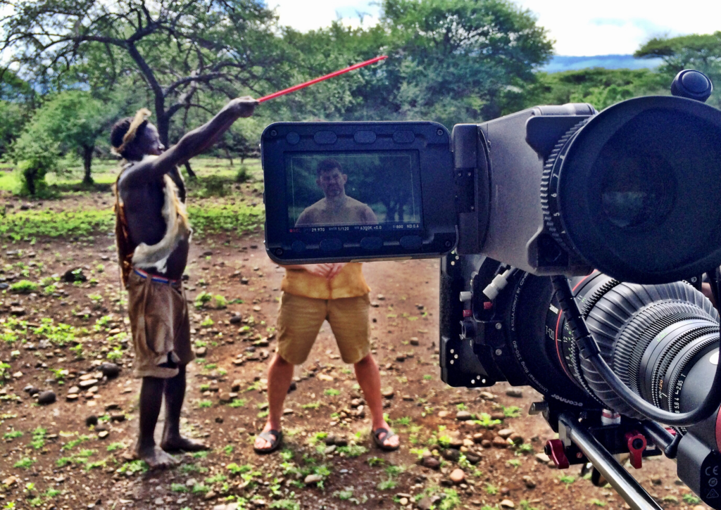 Photo of camera view of Bill filming the Great Human Race with African man holding boom mic