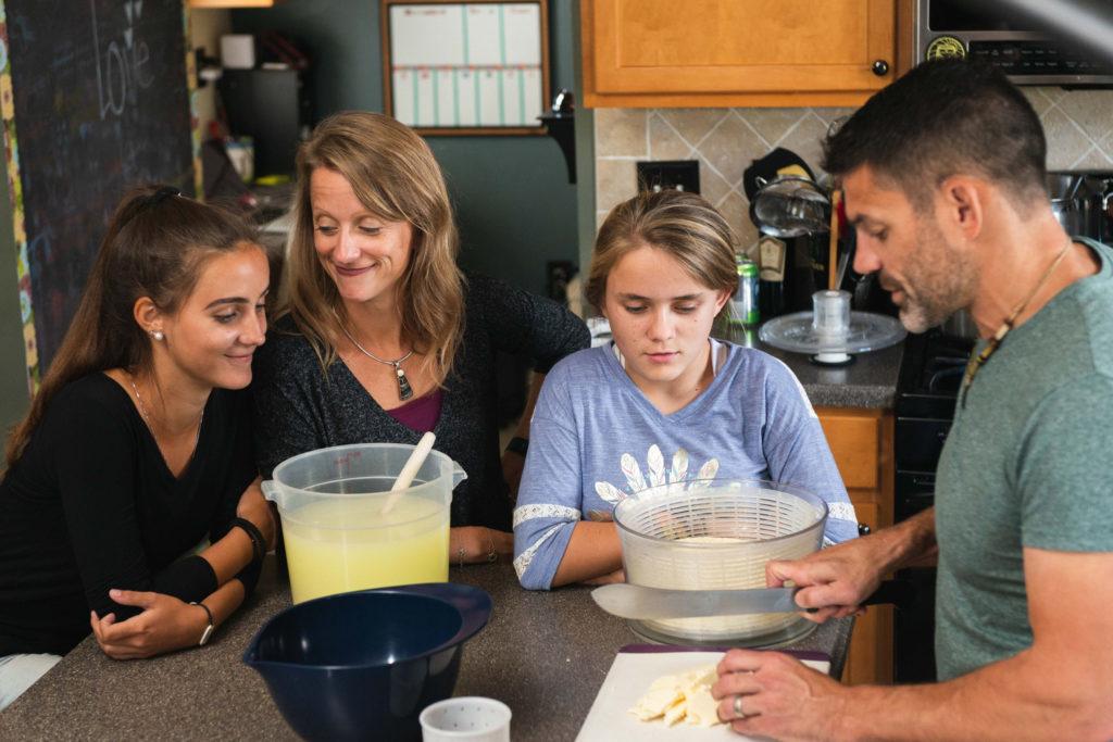 Brianna, Christina, Alyssa and Bill making cheese in their home kitchen